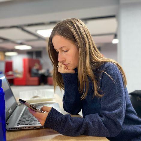 Ich sitzte in der Bibliothek und schaue auf mein Handy. Auf dem Tisch steht mein aufgeklappter Laptop.
