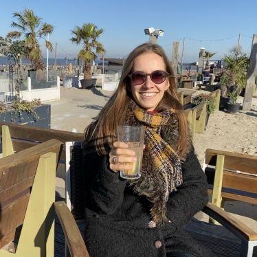 Ich sitzte draußen in einer Strandhütte und trinke einen Tee. Die Sonne scheint und ich lache. Im Hintergrund sieht man Palmen und den Rest der Terrasse.