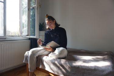 Tamara sitzt auf einem Bett und hält einen Terminkalender in der hand. Links im Hintergrund ist ein Fenster geöffnet.