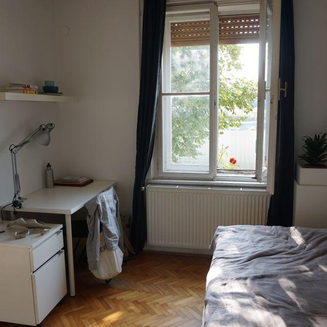 Hell eigerichtetes Zimmer mit Bett und Schreibtisch.