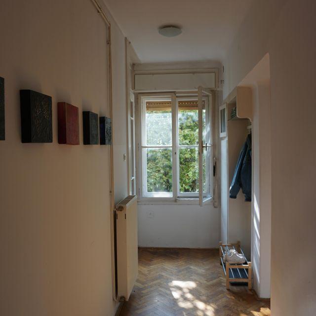 Langer schmaler Gang mit Fenster am Ende. Rechts hängt eine Jacke.
