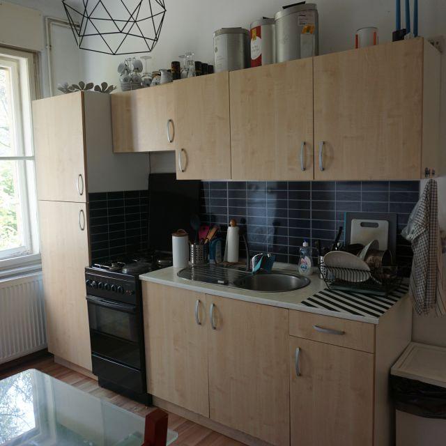 Küchenzeile aus hellem Holz und mit schwarzem Fließenspiegel.