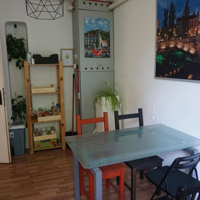 Esstisch aus Glas mit vier verschiedenen Stühlen. Im Hintergrund ist ein Regal zu sehen.