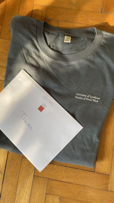 Graues T-Shirt mit dem Aufdruck: University of Ljubljana Faculty of Social Work. Auf dem Shirt liegt ein Briefumschlag auf den Tamara geschrieben wurde.