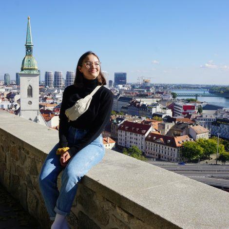 Tamara sitzt auf einer Mauer. Im Hintergrund sind die Dächer einer Stadt zu sehen.