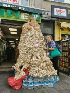 Sophie steht neben einem riesigen Haufen Knoblauch
