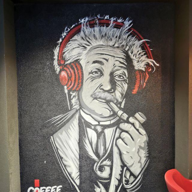 """Ein Bild von Albert Einstein, der hier rote Kopfhörer trägt, ist im """"Coffee Club"""" zu sehen. Hier treffen sich viele Studierende für ihre Pausen."""