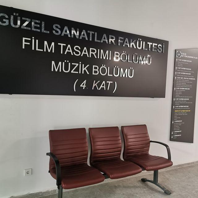 Drei rote Sessel laden ein, um an der Filmfakultät zu verweilen. Von dort hast du einen Blick auf die alten Bilder und Kameras.