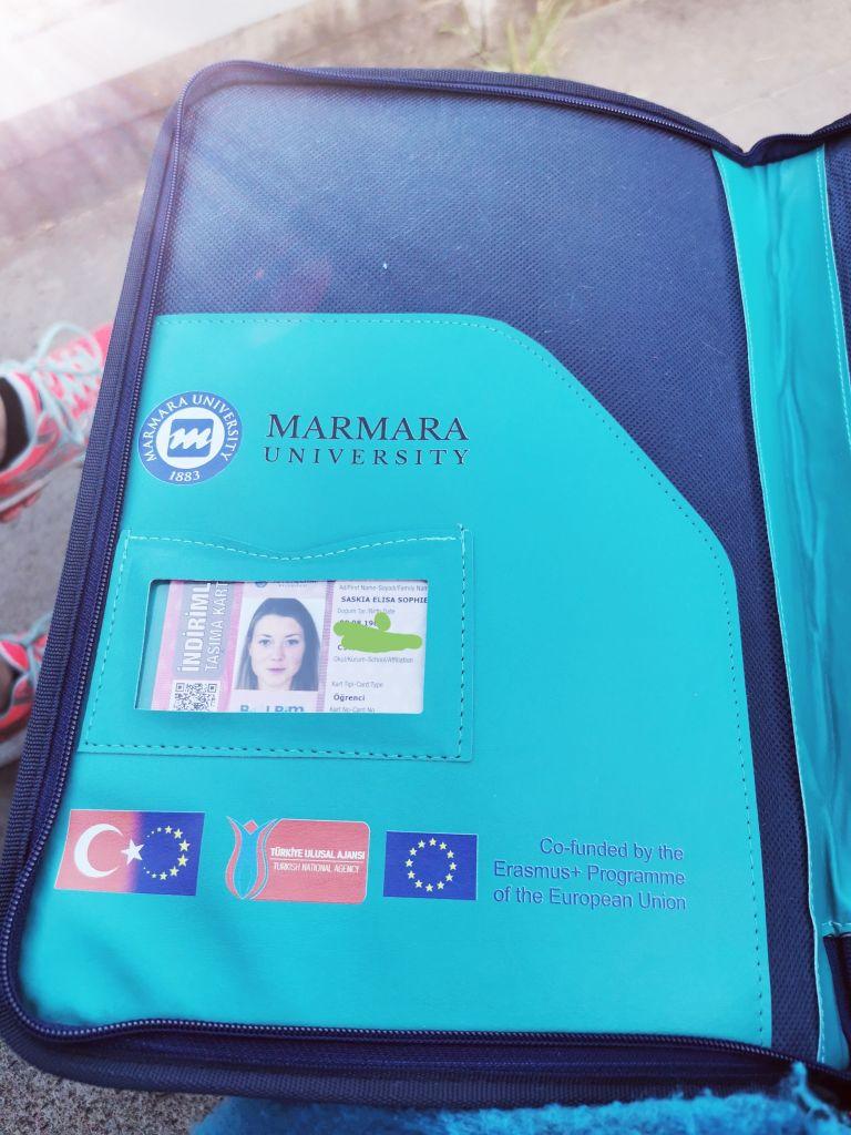 Blaue Mappe für Unterlagen. In einer Hülle steckt die studentische Metrokarte.