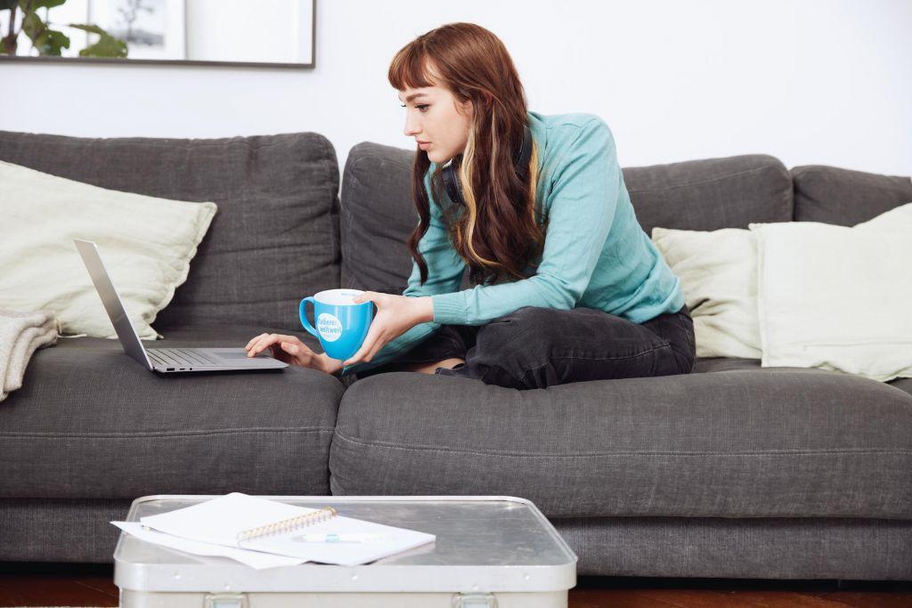 Frau sitzt mit Tasse auf dem Sofa und recherchiert am Laptop
