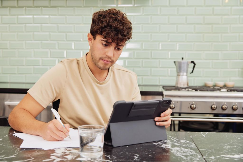 Mann sitzt mit Stift, Schreibblick und Tablet am Tisch