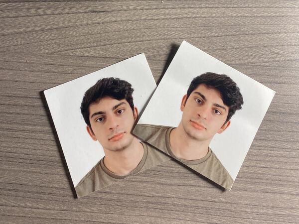Zwei Passfotos im amerikanischen Format sind zu sehen auf einem Schreibtisch. Sie haben ein anderes Format als das deutsche Passfoto